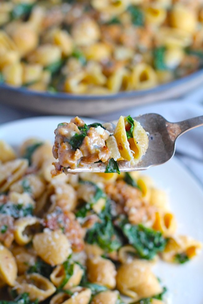 Fork with bite of shell Pasta with Italian Sausage and Kale that's also on a plate. It's loaded with a salty homemade Chicken Italian Sausage flavored with garlic and fennel in a parmesan, garlic and kale sauce.