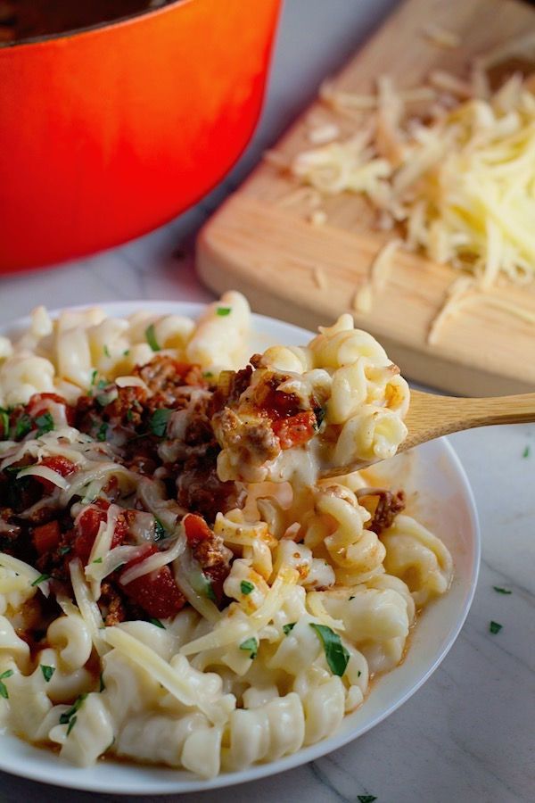 Chili Mac and Cheese on a plate with fork.  This Recipe has creamy and cheesy pasta topped with smokey, tangy, savory beef chili! #macandcheese #chilirecipes