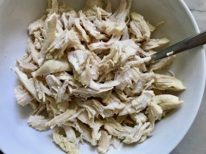 Shredded chicken for Creamy Chicken Enchilada Soup.  It's creamy, hearty, slightly spicy with green chiles and smokey seasonings that bring so much depth.  Corn tortilla strips act like the noodles in this soup!