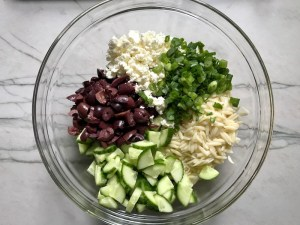 Cucumber, Kalamata Olives, Feta Cheese, Scallions, and orzo all separate in bowl for Greek Orzo Salad.