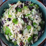 Greek Orzo Salad with Kalamata Olives, Cucumbers, and Feta Cheese in a bowl with spoon on side. It's mixed with a creamy lemon dressing that's bright and light!