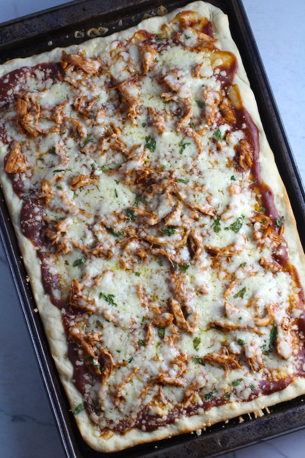 Whole BBQ Chicken Pizza in a rectangle sheet pan with homemade pizza crust, tangy and creamy BBQ sauce, hearty shredded chicken, cheddar cheese and coleslaw on top!