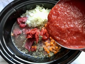 Pouring pureed tomatoes over raw beef, diced onion, carrots, and other ingredients in pot for Shredded Beef Ragu Recipe with Pappardelle. It's so easy to make and has a thick meaty texture and a super rich delicious flavor.