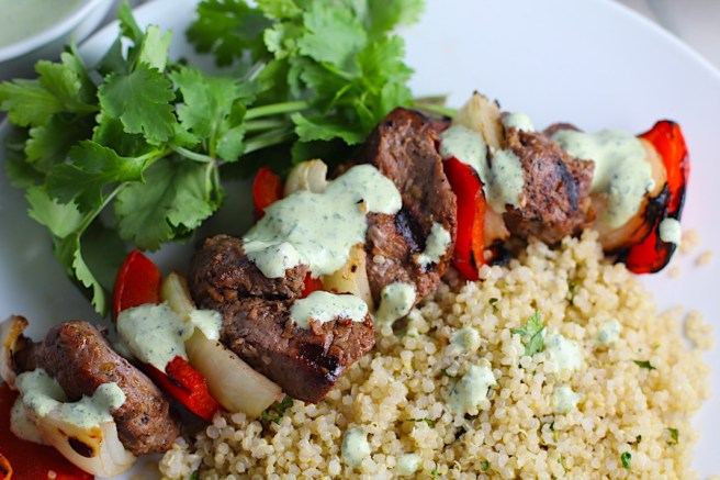 Garlic Steak Kabobs with red pepper and onion on plate with quinoa. Creamy Cilantro Sauce drizzled on top! #beefkabobs #steakkabobs