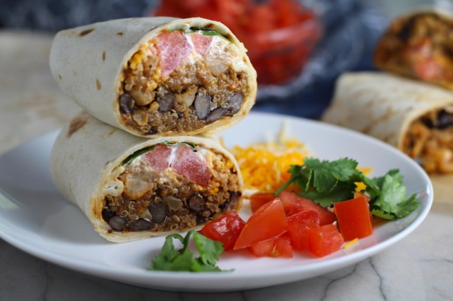 Quinoa Black Bean Burritos cut in half and stacked on plate. Packed with protein and fiber, but also cheese, tomato, cilantro, and sour cream!  The vegetarian 'meat' is taco-seasoned quinoa, black beans, and cauliflower.
