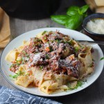 Shredded Beef Ragu Recipe with Pappardelle with a fork on plate with parsley, basil, parmesan, and bread on the table. It's so easy to make and has a thick meaty texture and a super rich delicious flavor.