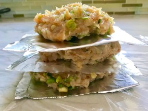 Raw chicken patties stacked between aluminum foil pieces for a Taco Chicken Burger recipe. The burger has smokey taco seasonings, cilantro, and scallions. Then on top are melty cheese, guacamole, lettuce, tomato, and chipotle mayonnaise!