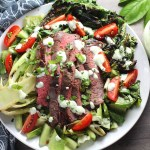 Sliced Grilled Flank Steak Salad Recipe on plate with grilled romaine, halved grape tomatoes, and creamy basil yogurt dressing.