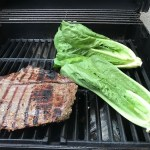 flank steak and romaine lettuce halves on gas grill for Flank Steak Salad Recipe with halved grape tomatoes, and creamy basil yogurt dressing.