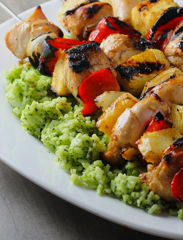 Green Rice on platter with chicken kabobs on top.  This Recipe takes white rice from plain to amazing with just 5 ingredients.  Filled with herbs and spinach, it has the perfect herby flavor.
