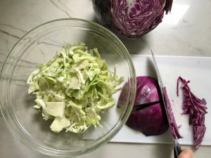 knife slicing purple cabbage with white cabbage in bowl on side for Korean Beef Tacos with flavorful Korean beef, crunchy Sesame Cabbage Slaw and a creamy, cool, Cilantro Lime Sriracha sauce!
