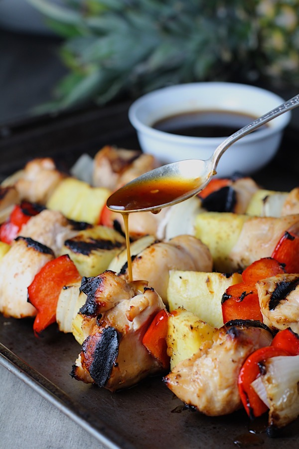 Spoon drizzling Sweet and Sour sauce over Chicken Kabobs with pineapple, onion, and red pepper on a pan.