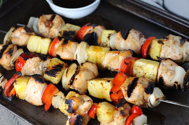 Sweet and Sour Chicken Kabobs with pineapple, onion, and red pepper on a pan.