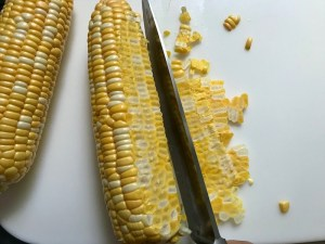 Knife cutting corn off cob for Creamy Corn and Blackened Chicken skillet dinner