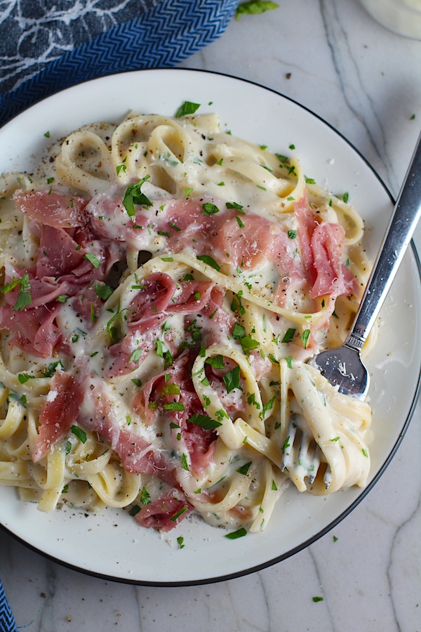 Easy Fettuccine Alfredo with Prosciutto on a plate with fork scooping pasta.  It's a creamy but lighter recipe without the heavy cream or butter, but still delicious!