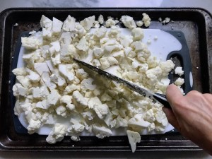 Knife cutting cauliflower on cutting board in sheet pan for Roasted Garlic Cauliflower Mash.