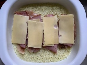 Sliced raw chicken with deli ham and slice of cheese on top for One Pot Chicken Cordon Bleu Bake. On the bottom you get flavorful rice topped with chicken, salty ham, nutty and melty swiss cheese, and a crunchy breadcrumb topping!
