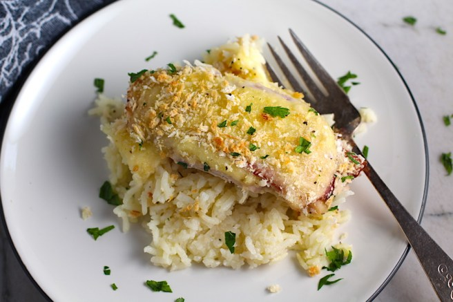 Piece of One Pot Chicken Cordon Bleu Bake on a plate with fork.  On the bottom you get flavorful rice topped with chicken, salty ham, nutty and melty swiss cheese, and a crunchy breadcrumb topping!