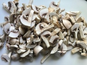 Sliced mushrooms for Creamy Green Beans and Mushrooms with Chorizo in a serving bowl are a creamy and savory side dish.