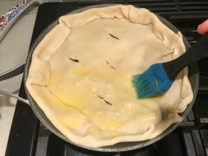 Pie crust on skillet for Empanada Beef Pie Recipe. It has a perfect flaky, buttery pastry on the outside with a savory, smokey, salty ground beef filling.  The best part is that everything cooks in one skillet!