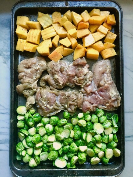 Sheet Pan Spanish Chicken thighs on a pan with Butternut Squash cubes in one side and Brussels Sprouts on the other! It's warm, hearty, and smoky.