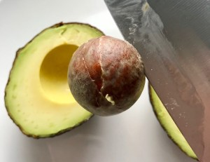 Knife pulling pit from avocado half for Avocado Crema recipe.