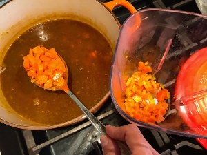 Spoon transfering carrots from pot to blender for Golden Carrot Ginger Soup Recipe.