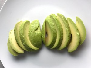 Peeled and sliced avocado fanned out on a plate for Taco Quinoa Bowls with Ground Beef, corn, cotija, tomatoes, and cilantro lime crema.