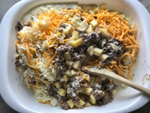 Wood spoon mixing cooked ground beef, sauce, shredded cheese, and cubed potatoes for Cheesy Hamburger Potato Casserole. It's an easy, yummy, and cozy weeknight family dinner.