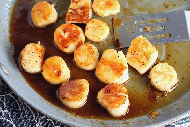 Glazed Pan Seared Scallops with Garlic and Honey in a pan with spatula