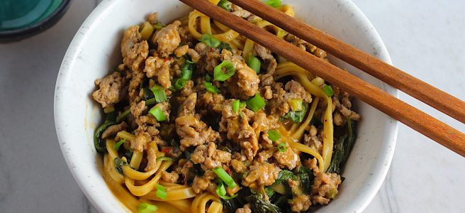 Dan Dan Noodle Recipe with Ground Chicken in a bowl. Chopsticks are sitting on top and scallion slices are on top.