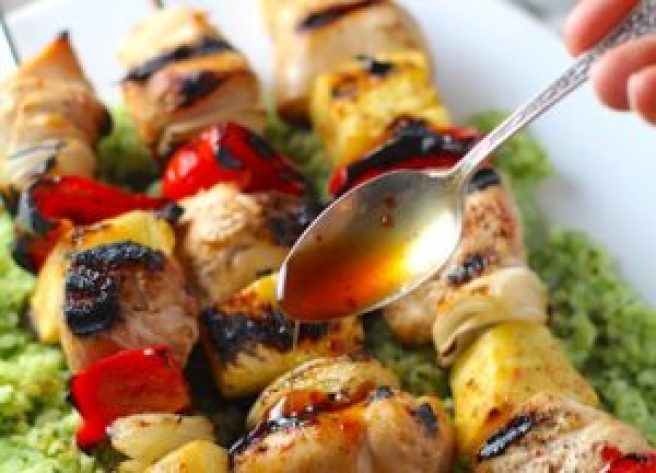Spoon drizzling Sweet and Sour sauce over Chicken Kabobs with pineapple, onion, and red pepper over Green Rice with basil, chives, and spinach.