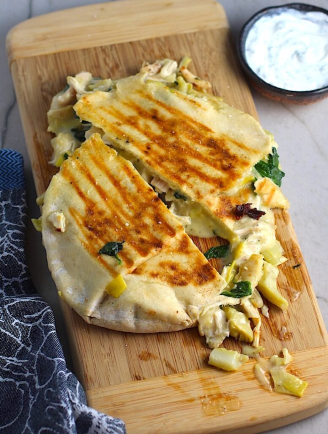 Spinach Artichoke Chicken Stuffed Pita is grilled and cut in half on a wood platter with filling oozing out. In the back is a small bowl of crema.