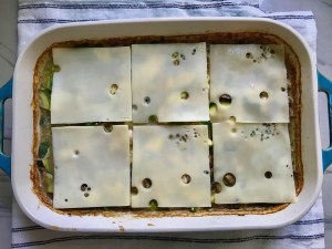6 slices of swiss cheese added to the top of Chicken Wild Rice Casserole with Zucchini and Mushrooms in a casserole dish