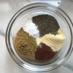Seasonings in a clear bowl on counter. From top clockwise, there is ground black pepper, garlic powder, chili powder, cumin powder, and salt for the Sheet Pan Pork Fajitas Recipe with red pepper, green pepper, and onion.
