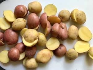 Halved red and gold creamer potatoes on cutting board for Sage Butter Potatoes.