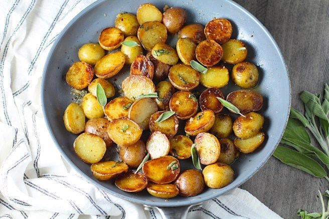 Crispy browned Sage Butter Potatoes in a skillet with garlic, sage butter glistening on top.