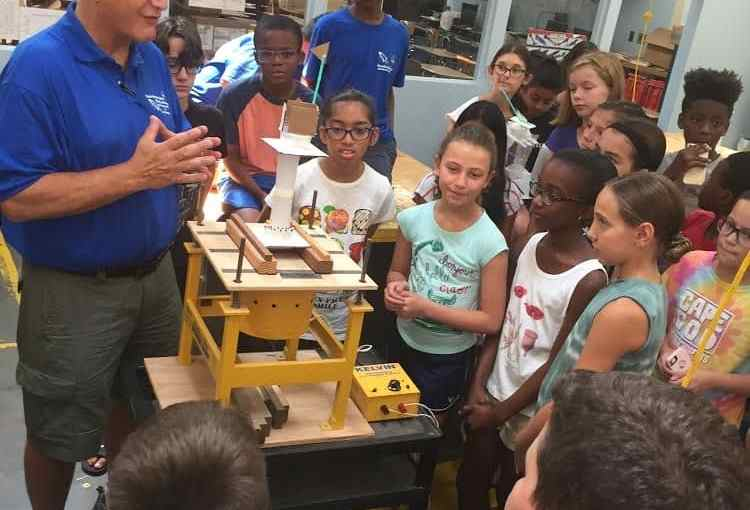 Technology Education Teacher Stephen G. May tests the students' towers on the earthquake machine