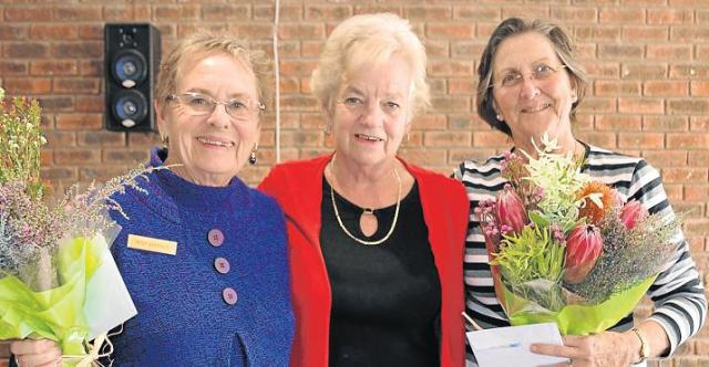 LEADING LADIES: Brenda Lear Hospice Bridge Drive organiser Trish Versfeld, left, and tournament director Elzabe Rodriguez, right, received bouquets from Hospice manager Zelda Elliott. Picture JON HOUZET