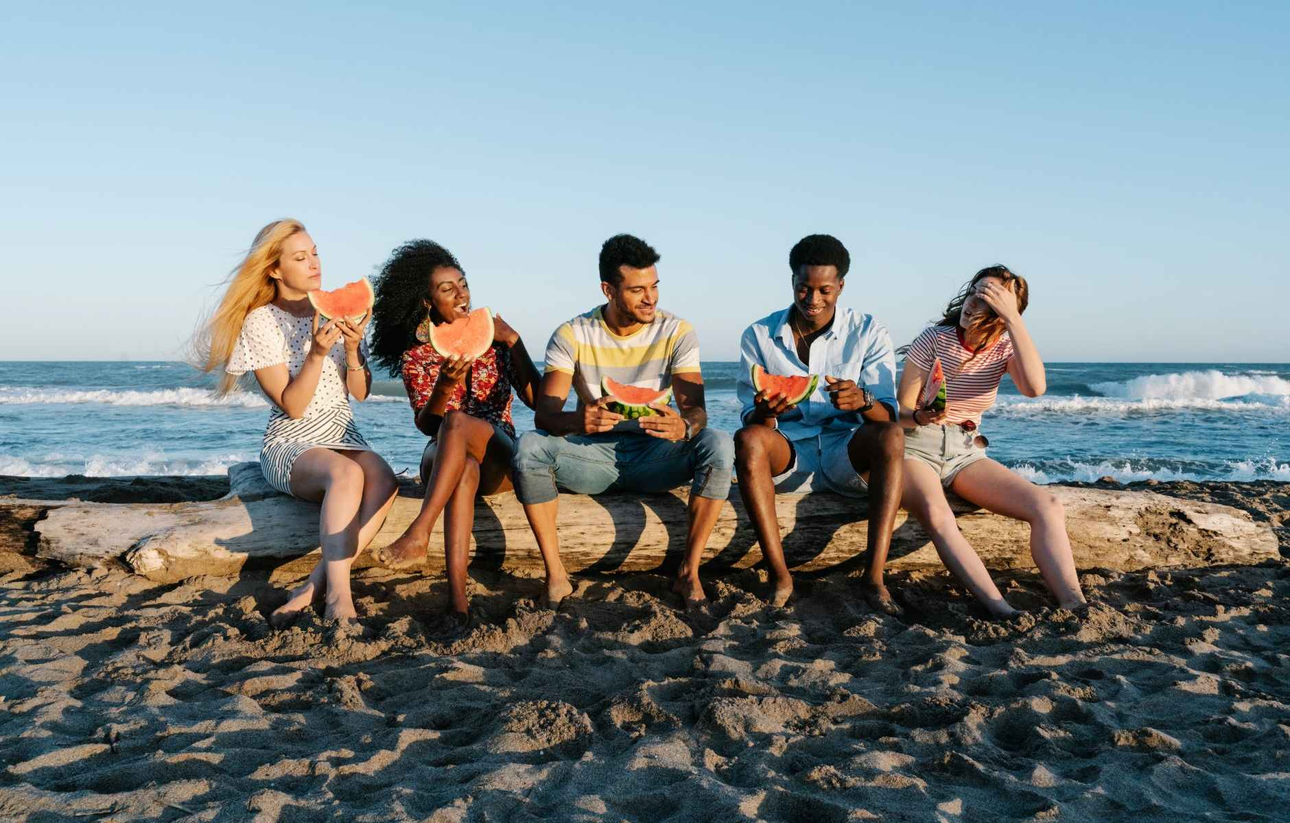 cheerful multiracial friends enjoying watermelon slices on sandy sea shore