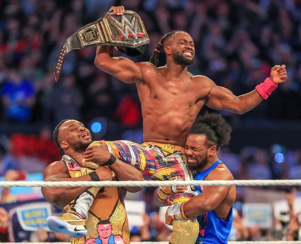 Kofi Kingston celebrates winning the WWE title with his New Day brothers