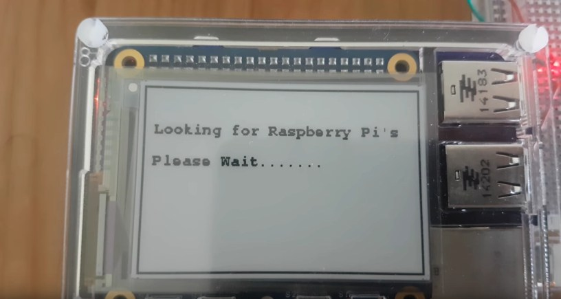 An e-ink screen on a Raspberry Pi showing the text Looking for Raspberry Pi's Please Wait