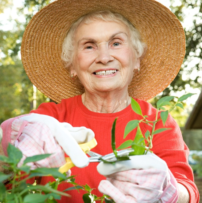 Senior woman working in the garden with her sun hat on
