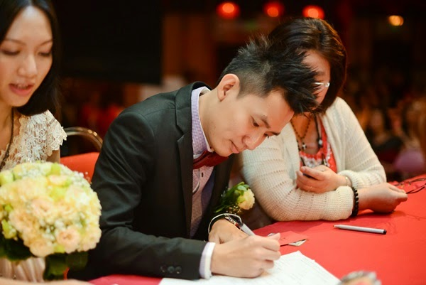 Clumsy Boy signs the marriage certification paper