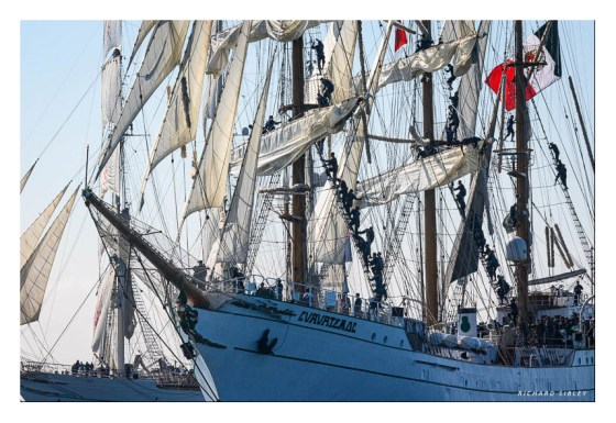 Dowsing sail onboard the Mexican barque Cuauhtemoc. Background vessel Shabab Oman
