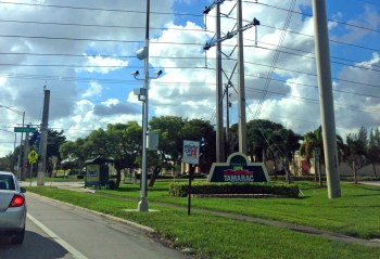 "Scam Cam Tower proudly displayed next to the ""Playful City USA"" sign in Tamarac"