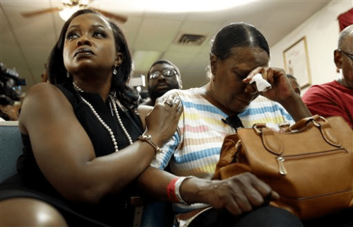 Phaedra Parks, left, comforts Desuirea Harris, the grandmother of Michael Brown, during a news conference Monday, Aug. 11, 2014, in Jennings, Mo. Michael Brown, 18, was shot and killed in a confrontation with police in the St. Louis suburb of Ferguson, Mo, on Saturday, Aug. 9, 2014. JEFF ROBERSON — AP Photo  ON SECOND THOUGHT SHE DID HAVE SOME FAT SUCKE OUT OF HER ARMS!