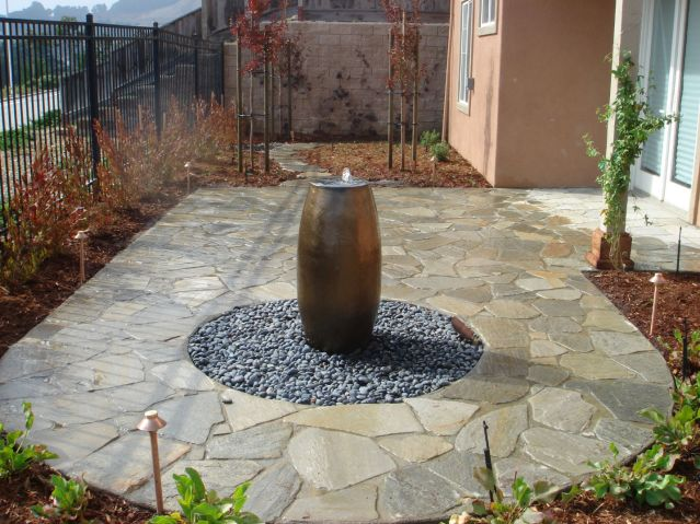 stone patio construction with vase fountain