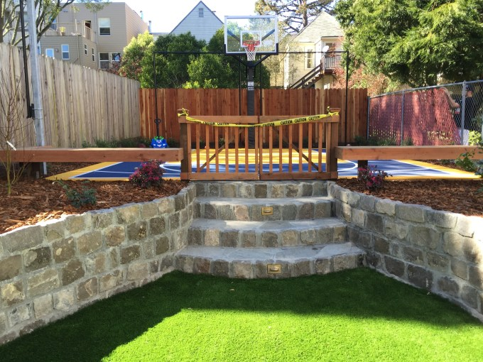 Sports backyard: basketball court has benches to watch the game play, as well as halogen lights