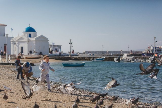 Boy chasing birds in Mykonos Town, Greece by Tami Keehn